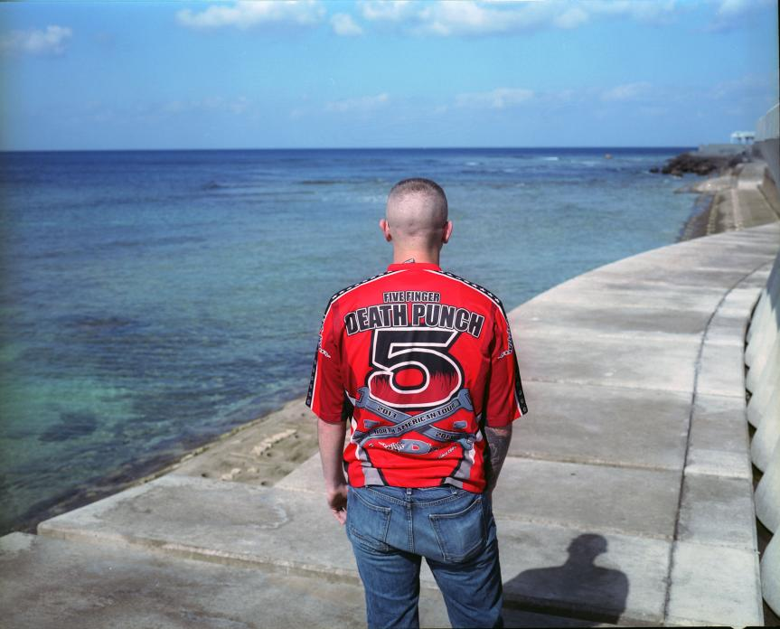 Off-duty Marine on seawall, Okinawa, Japan. 2014